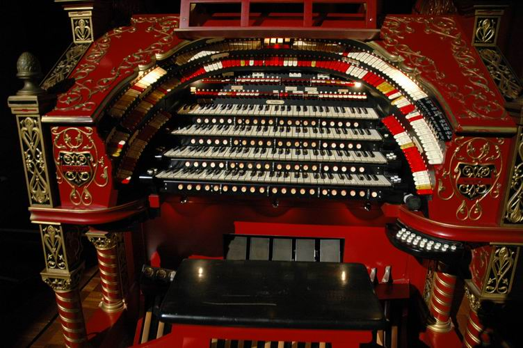 The organ console key manuals with pistons, stop rails, and expression pedals.